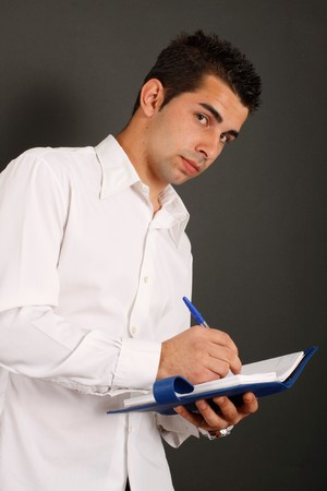 A man with a white shirt writing on a blue binder photo