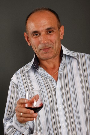 A spanish man drinks a glass of wine photo