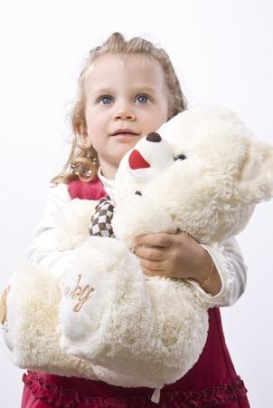 fondo azul: Niña de cabello rubio con ojos azules sosteniendo un oso de peluche