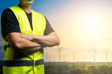 Green energy concept : Maintenance technician wear reflective shirts over black clothes. There is a background in a field of wind turbines for generating electricity.