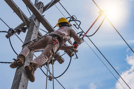 The power lineman use clamp stick (insulated tool) to closing a transformer on energized high-voltage electric power lines. The power lineman must be trained because it is a risky job. Zdjęcie Seryjne