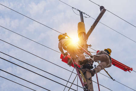 Two linesmen use insulated equipment to repair and maintain high-voltage distribution systems. The operation is done without power outage. Is a risky job, the operator must be trained.
