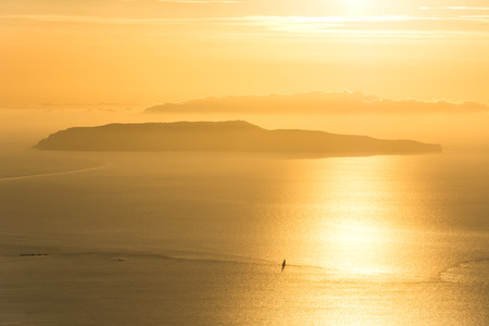 Golden sunset over ocean with lonely sailboat and small island