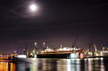 Large container ship at the dock at the Hamburg harbor at night