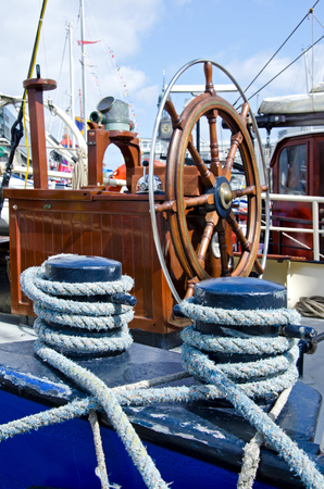 Ship's wheel and ropes on a historic boat