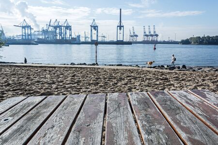 Waterfront with beach and harbor cranes in the background in Hamburg, Germany