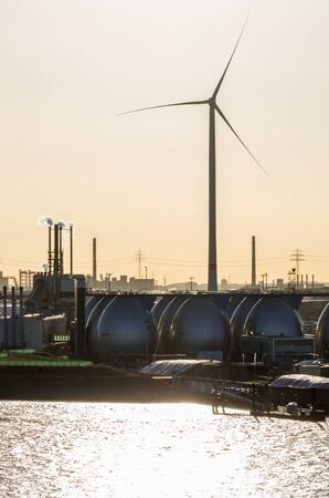 Wind turbine and gas storage units in industrial area at the harbor Imagens