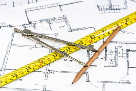 Compass calipers and pencil lying on construction plan