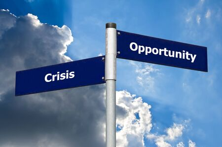 Street sign in front of dark clouds symbolizing contrast between 'crisis' and 'opportunity'