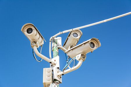 Surveillance cameras in front of blue sky