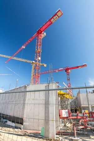Vertical shot of big construction site with construction fence and cranes