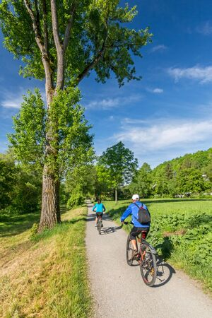 Cyclists riding down a pathway in a park in spring