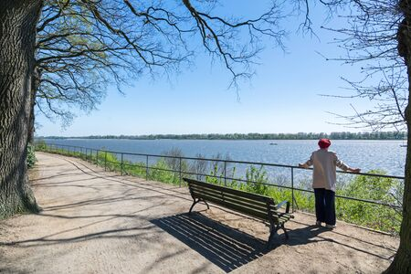 Older woman stands on the Elbe bank and looks into the distance Stock Photo