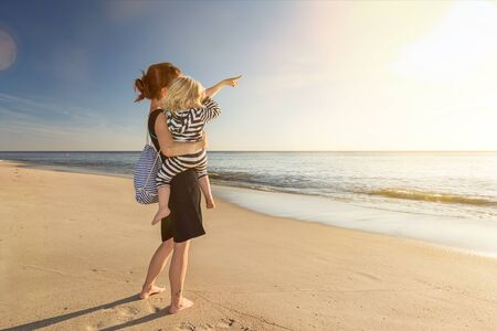 Young woman at the beach holding toddler in her arm and pointing towards the ocean and the sun Stock fotó