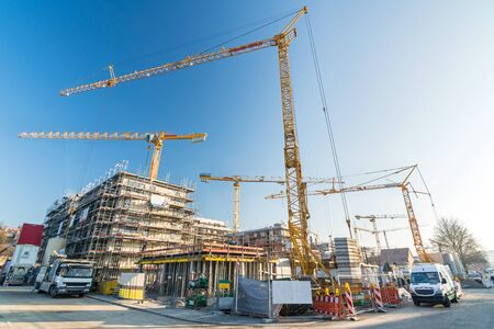 Construction site and shell construction of offices and apartment buildings with many cranes and construction vehicles Stockfoto - 133485740