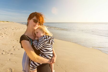 Young woman with child in her arms relaxes on the beach and enjoys the sunset Stock fotó