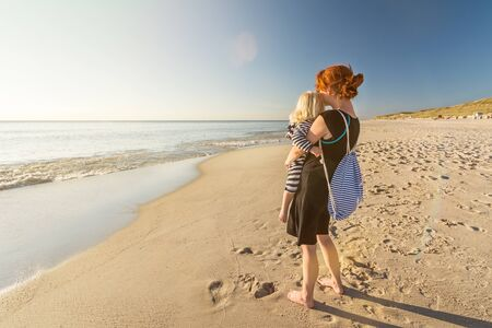 Woman is standing on a lonely beach with her child in her arms, looking into the sunset