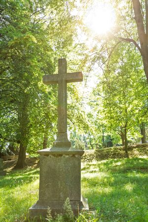 Sun shining on a grave cross at an old cemetery Stock Photo