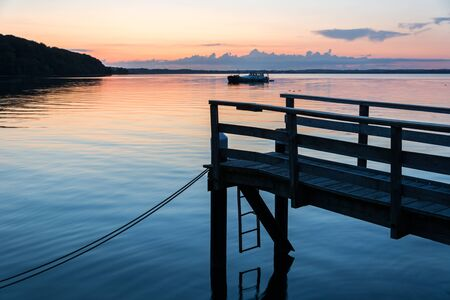 Wooden pier at the shore of the Baltic Sea during a beautiful colorful sunset