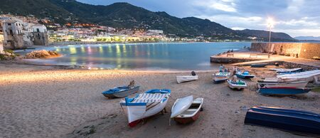 Panorama night shot of beautiful bay and fishing boats in Cefalu, Sicily, Italy Stockfoto