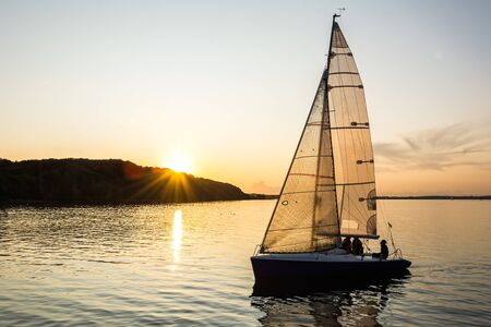 Sailing boat sailing into the harbor during beautiful sunset