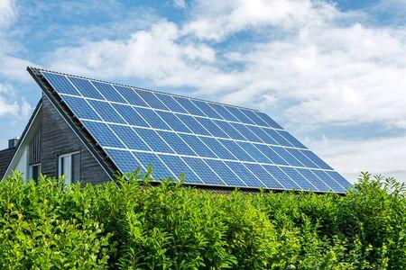 Haus mit Sonnenkollektoren auf dem Dach an einem sonnigen Tag