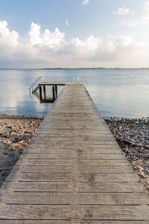 Wooden pier leading towards the ocean Фото со стока