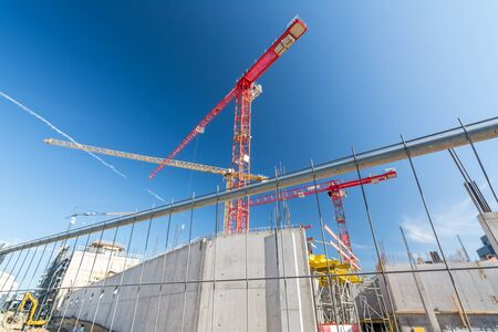Large construction site with construction fence and cranes
