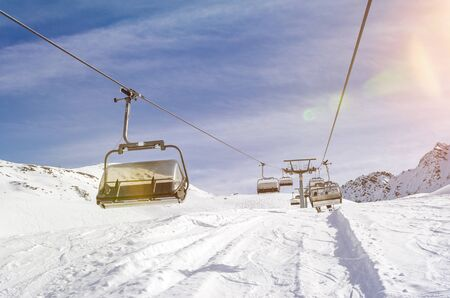 Chairlift in a ski resort in winter with scenic lens flare Фото со стока