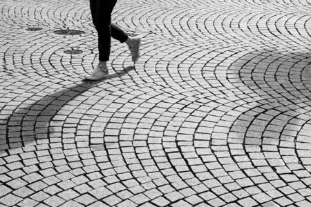 Feet and legs of a person walking on cobbled street