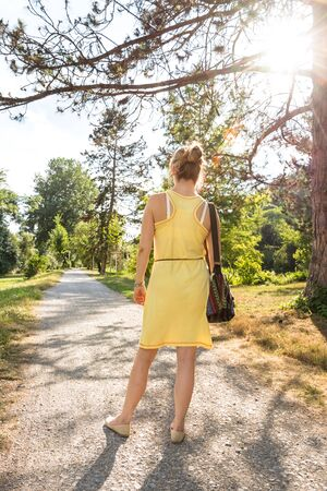 Young woman in a stylish summer dress standing in a park in summer