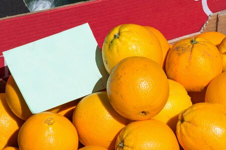 Fresh organic oranges at the farmers market with copy space on cardboard sign