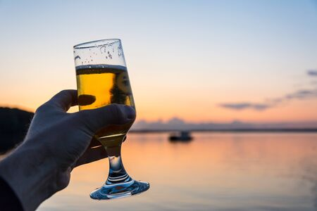 Having a fresh cold beer at a seashore during a beautiful sunset