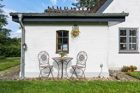 Peaceful garden with two chairs in front of whitewashed historic house in Northern Germany Фото со стока