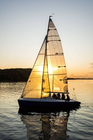 Sailing boat sailing into the harbor during beautiful sunset with the sun shining through the sail