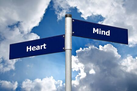 Street sign in the front of a cloudy sky representing a choice between listening to the heart or the mind