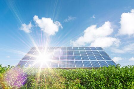 House with solar panels on the roof and scenic sun rays Фото со стока