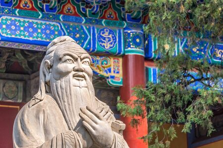 Closeup of Confucius statue in front of colorful ancient temple with beautiful ornaments