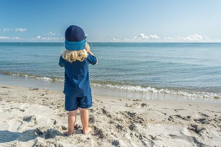 Young child standing at the beach and looking at the beautiful blue ocean