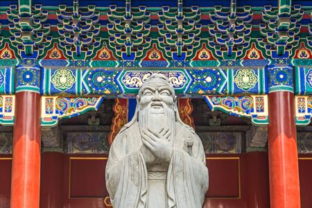 Confucius statue in front of colorful ancient temple with beautiful ornaments Фото со стока