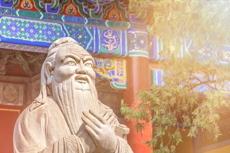 Closeup of Confucius statue in front of colorful ancient temple in scenic sunlight