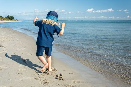 Young child having fun and walking down the beach at the beautiful blue ocean Фото со стока