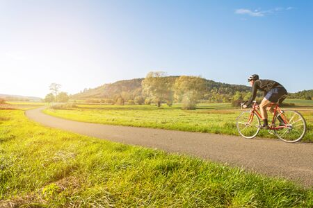 Cyclist on a racing bike in scenic autumn landscape