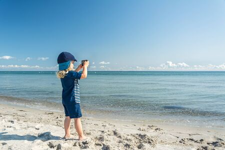 Young child standing at the beach and taking a photo of the beautiful blue ocean