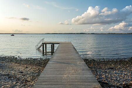 Muelle de madera en el tranquilo Mar Báltico en la pintoresca luz del atardecer
