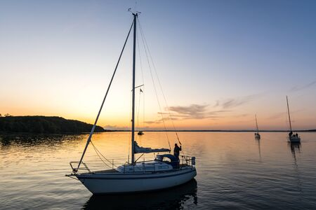 Sailing boats coming back into the harbor during beautiful sunset