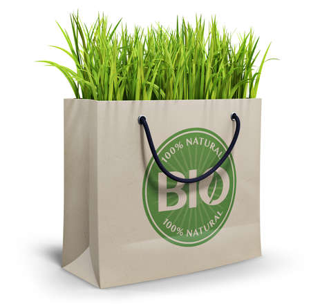 Bio 100% natural, shopping bag filled with grass, isolated on white background photo