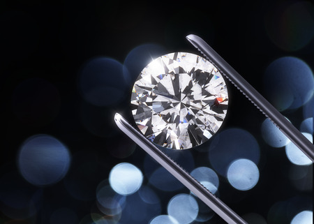 Luxury diamond in tweezers closeup with dark background