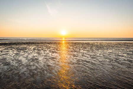 Beautiful sunset on the sand beach coast in Denmark. Sunny nature background. Clear sky with sun