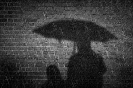 Noir style autumn rainy night in city. Mother with children in rain protected with umbrella. Two people cast a shadow on old brick wall. Stockfoto